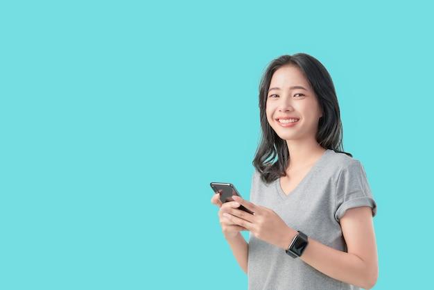 Smartwatch asiatico sorridente della tenuta della donna dei giovani e smartwatch di usura isolati su fondo blu-chiaro. Foto Premium