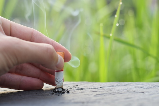 Smettere di fumare smettere di fumare concetto, sigaretta caduto a mano scese sul tavolo di legno per smettere di fumare. Foto Premium
