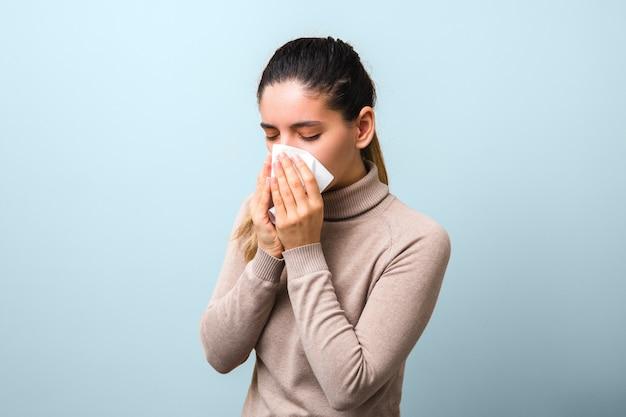 Smetti di diffondere coronavirus. giovane donna malata con mosca o virus che starnutisce e tossisce in una maschera o un tovagliolo che sembra molto senza speranza Foto Premium