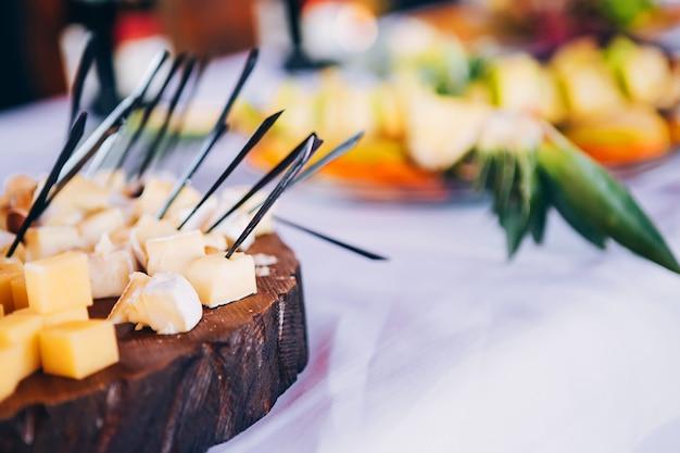 Smorgasbord. colazione a buffet. servizi di catering. piccoli panini, formaggio e uva su uno spiedino, torte piccole, pomodorini con verdure, olive con carne, un piatto di formaggi. Foto Premium
