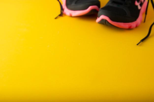 Sneackers delle scarpe sportive, usura della palestra, sopra fondo giallo con lo spazio della copia. Foto Premium
