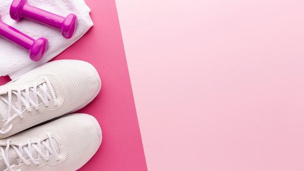 Sneakers bianche e pesi rosa con spazio di copia Foto Gratuite