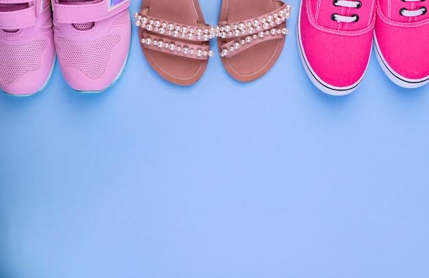Sneakers rosa, stivali di gomma e sandali per una ragazza su sfondo blu. scarpe diverse. Foto Premium