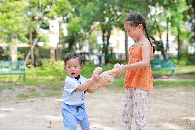Soddisfa la sorellina asiatica che si arrampica sull'orsacchiotto con il suo fratellino. Foto Premium