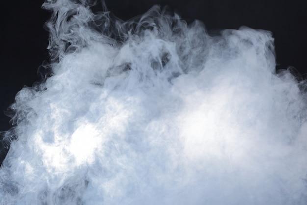 Soffi soffici densi di fumo bianco e nebbia su sfondo nero Foto Premium