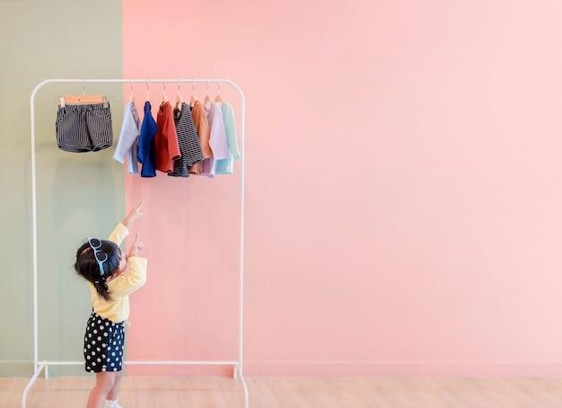 Soft focus of happy kids puntando le mani al rack di stoffa per la scelta dei propri abiti Foto Premium