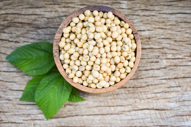 Soia, soia nei prodotti agricoli di una ciotola di legno sui precedenti di legno / fagioli di soia asciutti e foglia verde Foto Premium