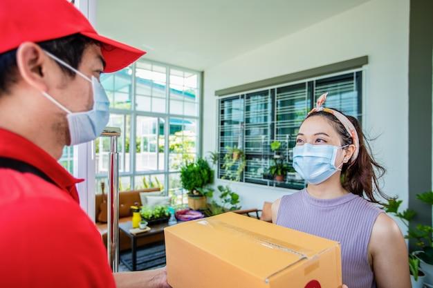 Soldati asiatici di consegna che indossano un'uniforme rossa con un cappuccio rosso e una maschera facciale che maneggiano le scatole di cartone Foto Premium