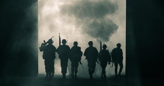 Soldati tailandesi forze speciali squadra uniforme piena camminando azione attraverso il fumo e tenendo la pistola a portata di mano Foto Premium