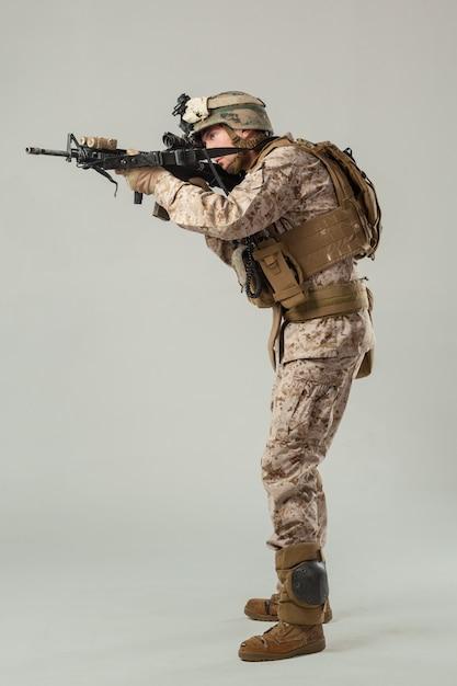 Soldato in mimetica che tiene il fucile Foto Premium