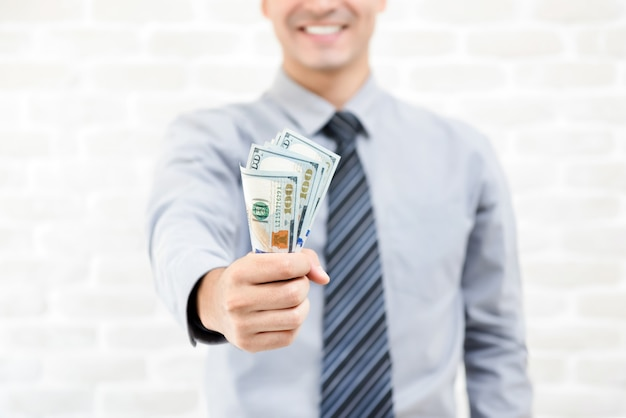 Soldi, banconote del dollaro degli stati uniti, in mano dell'uomo d'affari Foto Premium