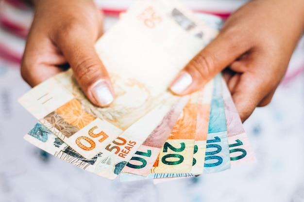 Soldi brasiliani - note reali - valuta brasiliana - concetto di finanza - investimenti - ricchezza - soldi della tenuta della donna. Foto Premium