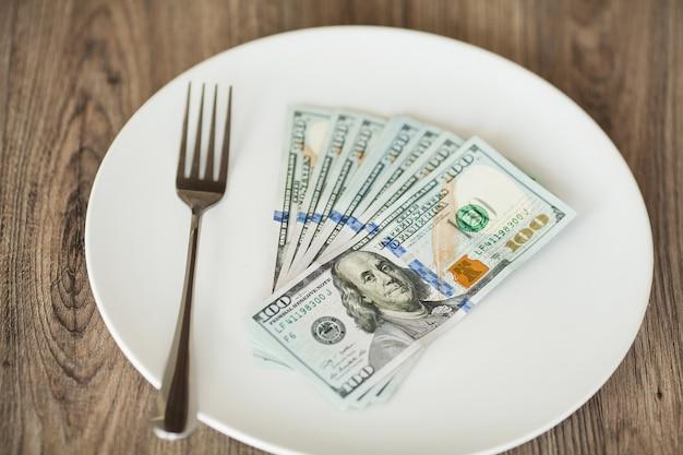 Soldi che si trovano sul piatto con la forcella. foto di dollari. corruzione avida. idea di bustarella Foto Premium
