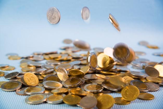 Soldi di caduta delle monete su fondo blu Foto Premium