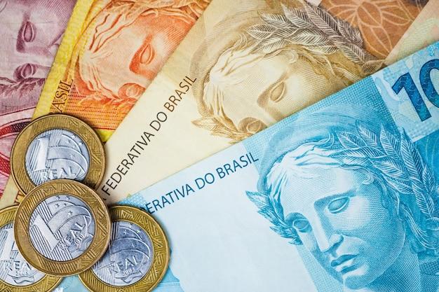 Soldi e monete brasiliani su una tavola. Foto Premium