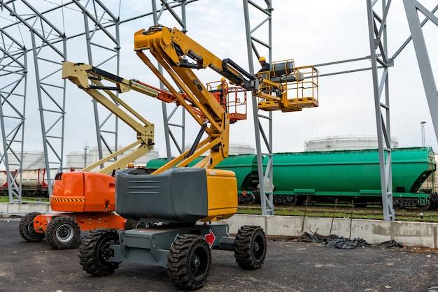 Sollevi con il lavoro della piattaforma nel campo di costruzione del capannone del magazzino. Foto Premium