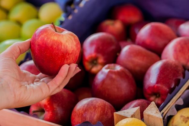 Solo i migliori frutti e verdure. bella giovane donna azienda mela. donna che acquista una mela rossa fresca in un mercato verde .. donna che acquista mele organiche al supermercato Foto Gratuite
