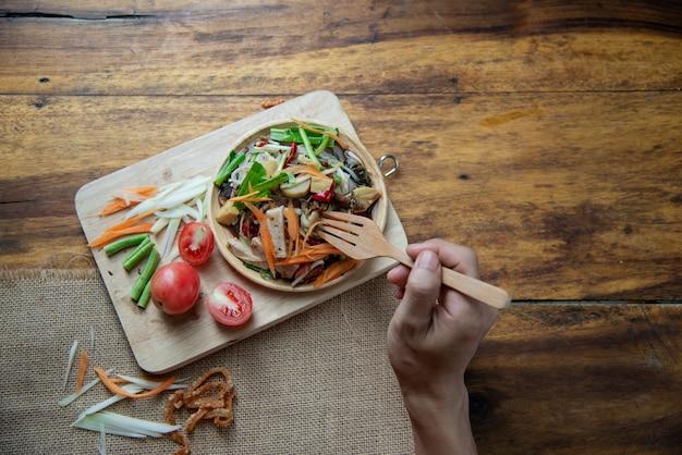 Som tam thai, insalata di papaia tailandese su fondo di legno Foto Gratuite