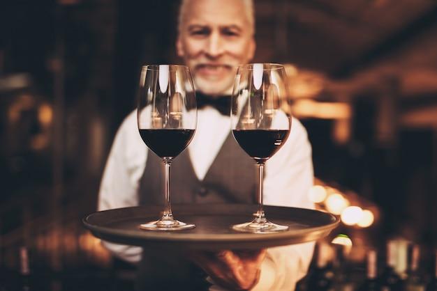 Sommelier con papillon tiene vassoio con bicchieri di vino. Foto Premium