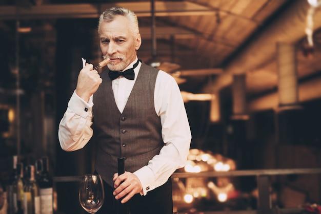 Sommelier sta sniffando cork of wine in restaurant Foto Premium