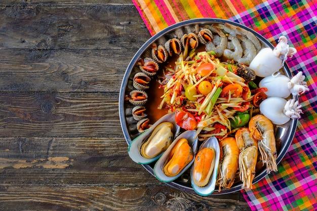 Somtum seafood, con gusci di gamberetti, posto in un vassoio, splendidamente posizionato su un tavolo di legno Foto Premium
