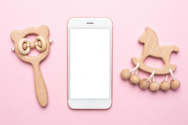 Sonagli e giocattoli di legno del bambino e del telefono cellulare sul rosa Foto Premium
