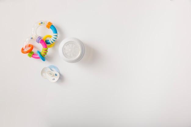 Sonaglio; ciuccio e bottiglia per il latte isolato su sfondo bianco Foto Gratuite