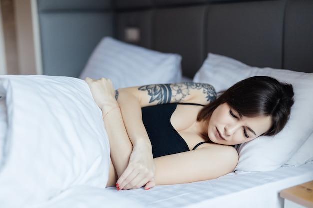 Sonnolenta giovane donna sdraiata a letto non vuole svegliarsi Foto Gratuite