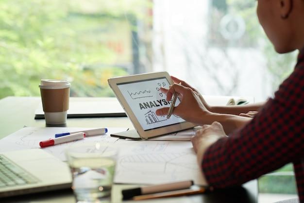Sopra la vista shoukder della persona irriconoscibile che esamina il grafico di analisi su tablet pc Foto Gratuite