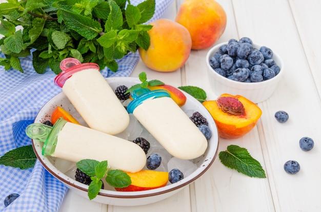 Sorbetto delizioso del yogurt di dieta con purea di pesche su un bastone su un fondo di legno bianco Foto Premium