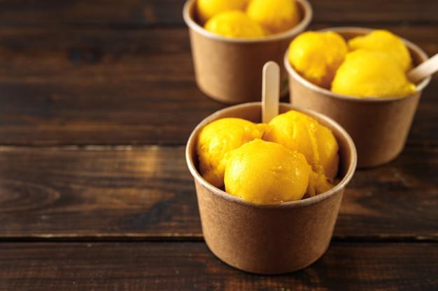 Sorbetto di ghiaccio delizioso del mango in tazze di carta su fondo di legno nello stile rustico Foto Premium