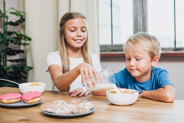 Sorella che versa il latte per suo fratello Foto Gratuite