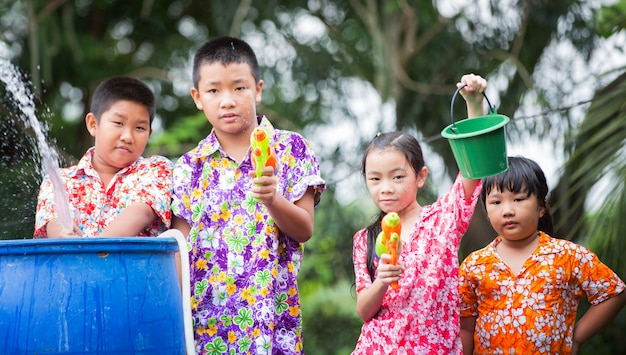 Sorella e fratelli giocano a pistole ad acqua al festival di songkran Foto Premium