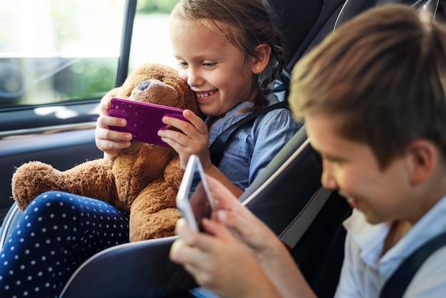 Sorella e fratello che giocano con i dispositivi digitali nell'automobile Foto Premium
