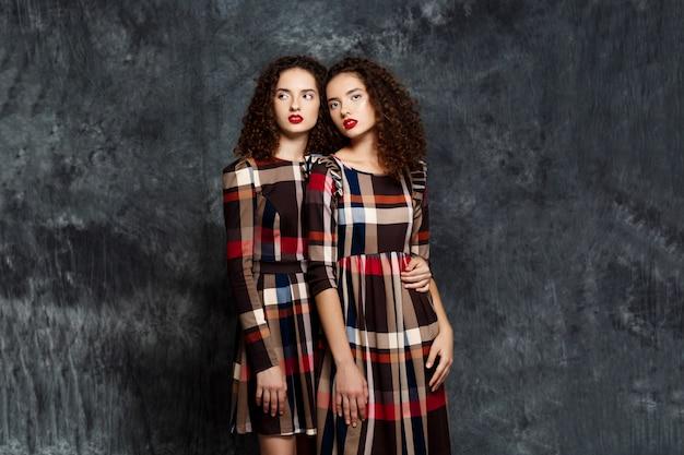Sorelle gemelle in abiti in posa sul grigio Foto Gratuite