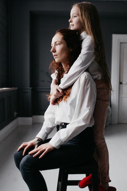 Sorelle giovani e adulte si abbracciano nel loft, rappresentando amicizia, fiducia, somiglianza Foto Premium