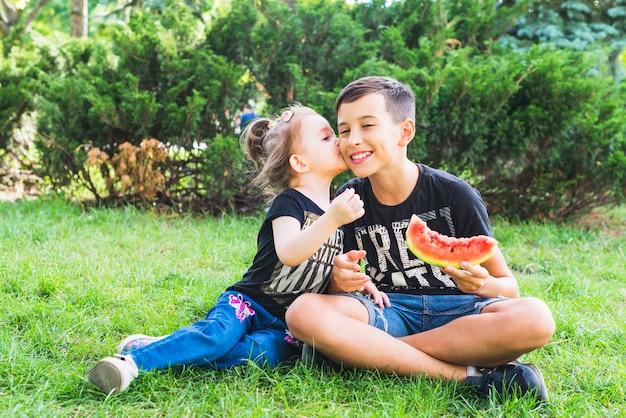 Sorellina che bacia il fratello tenendo la fetta di anguria Foto Gratuite