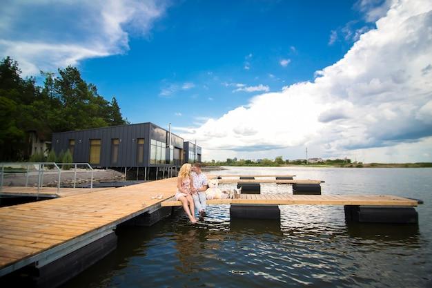 Sorpresa per un appuntamento romantico. un giovane ragazzo e una donna su un molo di legno. abbraccia e bacia mentre sei seduto sul molo. storia d'amore romantica Foto Premium