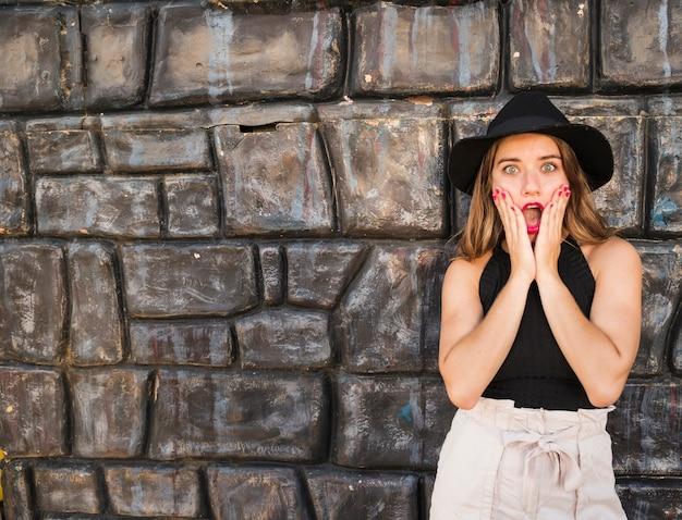 Sorpreso giovane donna in piedi davanti al muro Foto Gratuite