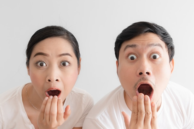 Sorpreso sul viso divertente paio in t-shirt bianca e sfondo bianco. Foto Premium
