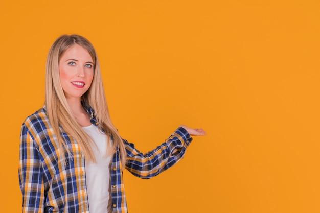 Sorridendo una giovane donna che presenta qualcosa contro uno sfondo arancione Foto Gratuite