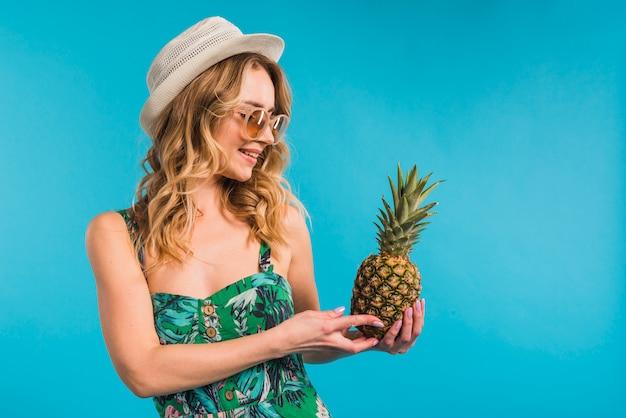 Sorridente attraente giovane donna in abito con cappello e occhiali da sole guardando ananas fresco Foto Gratuite
