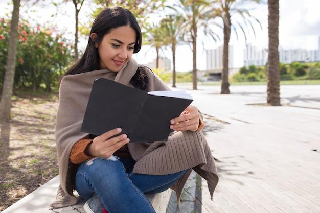 Sorridente bella donna lettura quaderno e studiare all'aperto Foto Gratuite