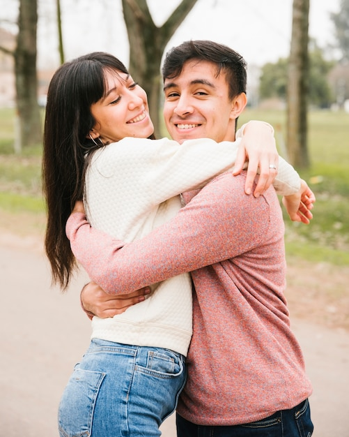 Sorridente coppia carina abbracciando nel parco Foto Gratuite