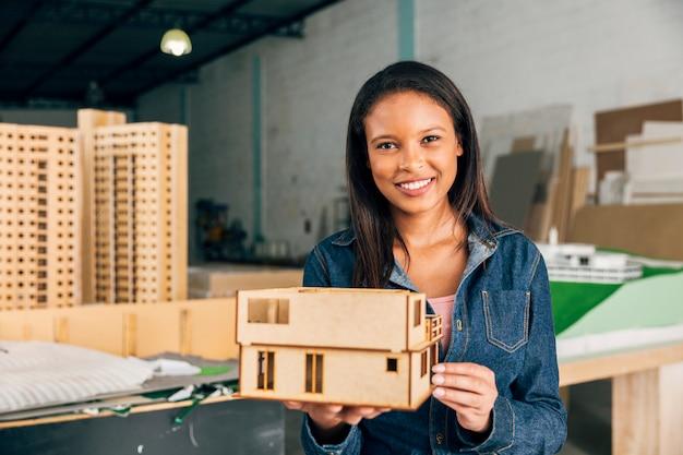 Sorridente donna afroamericana con il modello di casa Foto Gratuite