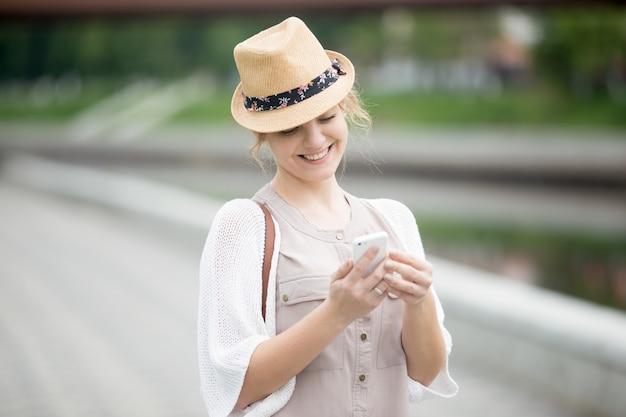 Sorridente donna con cappello guardando il suo cellulare
