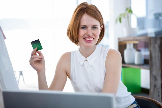 Sorridente donna d'affari hipster seduto alla sua scrivania, in possesso di una carta di credito Foto Premium