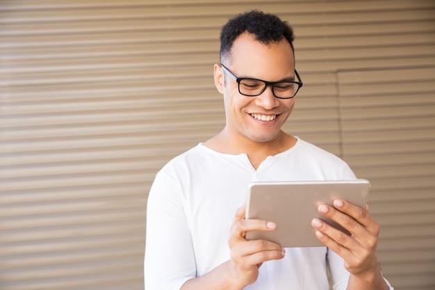 Sorridente giovane razza mista uomo lavorando su tablet. vista frontale Foto Gratuite