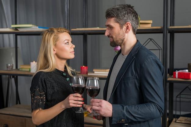 Sorridente maschio e biondo femminile clanging bicchieri di bevanda in camera Foto Gratuite