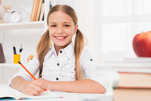 Sorridente ragazza bionda scuola elementare facendo i compiti Foto Gratuite